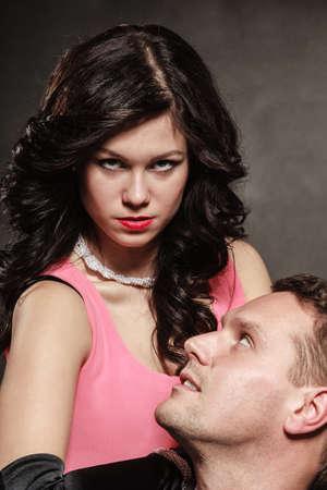 domination: Mujer en el control del hombre, la hembra atractiva controla su chico. Estudio tirado en el fondo gris negro.