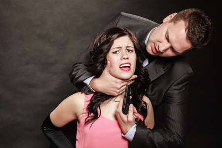 man holding gun: Scene of violence with firearm between men and women. Elegant man holding gun and neck of sitting lady on black and grey background in studio.