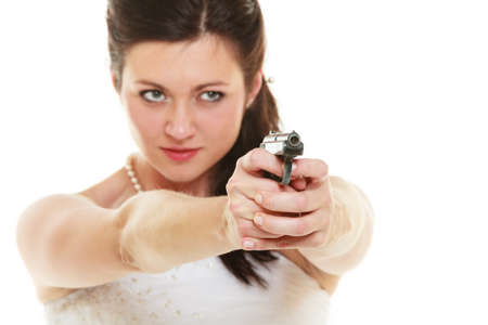 unloved: Wedding Day. Angry betrayed bride concept. Woman in white dress with gun isolated on white. Studio shot.