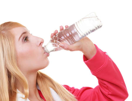 Fitness woman sport girl with white towel on her shoulders drinking water from bottle isolated on white. Studio shot. Training and workout. photo