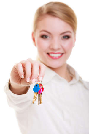 accomodation: Happy woman real estate agent holding set of keys to new house or car. Property business and accomodation or home buying ownership concept, isolated on white background