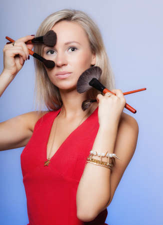 makeover: Cosmetic beauty procedures and makeover concept. Attractive woman red dress holds makeup professional brushes near face. Make-up applying with accessories tools. Blue background