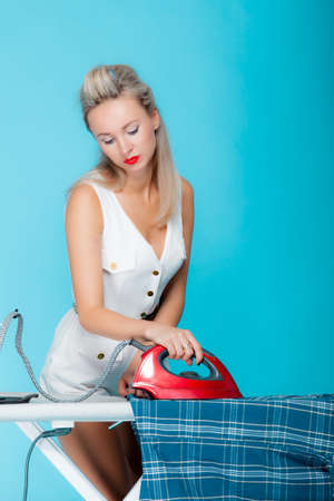 Sexy girl retro style ironing male shirt, woman housewife in domestic role. Traditional sharing household chores.  Pin up housework.  Vivid blue background photo
