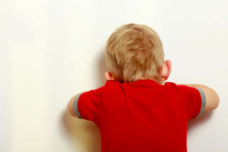 blind child: Happy childhood. Back view. Blond boy child covering his face. Kid preschooler playing hide-and-seek or blind man Stock Photo
