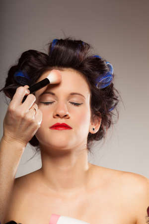 visagiste: Cosmetic beauty procedures and makeover concept. Makeup artist visagiste applying powder with brush on face of fashion model.