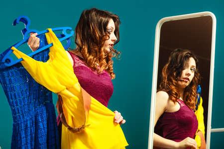 Moda y compras. Mujer que se prepara para partido, tratando vestido elegir la ropa. Atractiva mujer joven comprador busca en el espejo, de pie en la tienda de ropa.