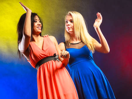 making dresses: Party, celabration, carnival. Two attractive funny dancing women making high five hands gesture in dresses on colorful background.