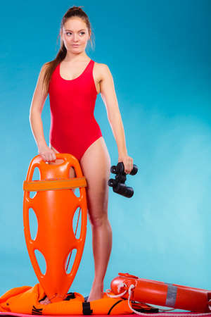 lifesaving: Accident prevention and water rescue. Attractive female model in lifeguard outfit on duty with binocular keeping float lifesaver equipment on blue Stock Photo