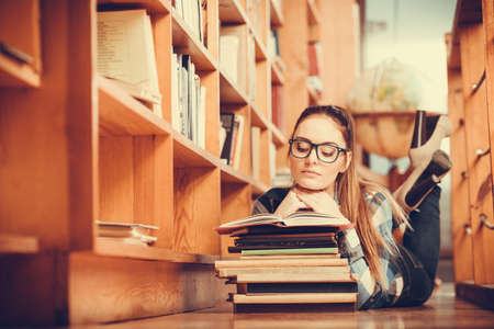 library: Clever female student girl in glasses lying on floor in college library with stack books reading
