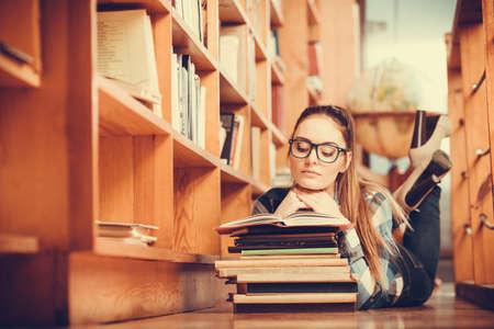 gafas: Muchacha del estudiante femenino listo en vidrios acostado en el piso en la biblioteca de la universidad con la lectura de libros de la pila Foto de archivo
