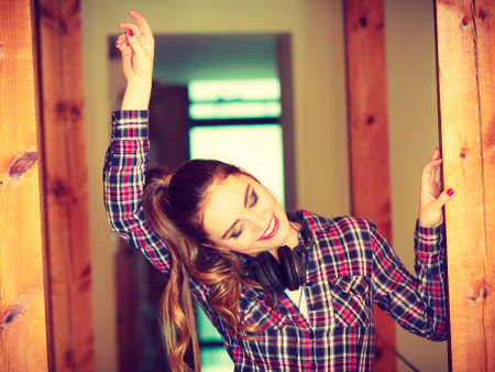 Music and technology concept - smiling teenage girl wearing plaid shirt with headphones listening mp3 dancing at home Stock Photo