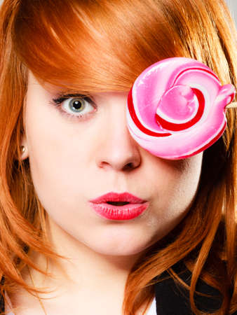 Closeup funny young woman holding candy. Redhair girl with pink lollipop having fun., covering her eye. photo