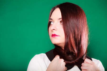 pelo rojo: El cuidado del cabello, peluquer�a y estilista. Joven mujer de pelo rojo con el pelo largo en el cuello en el fondo verde. Estudio de disparo.