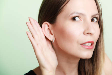 blab: Female hand to ear listening on green. Gossip girl with palm behind ear spying. Young business woman listening secret. Stock Photo
