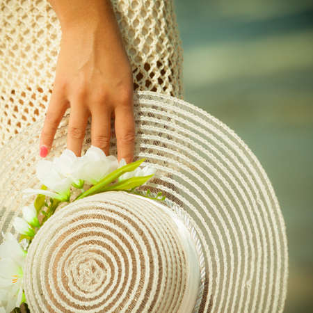 head protection: Summer fashion, head protection. Closeup female hand holding white hat decorated with flowers outdoors. Woman walking on seashore