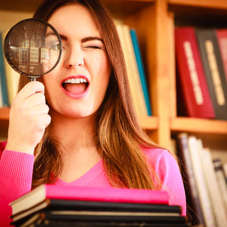 lupa: Investigation exploration education concept. Closeup intelligent funny student girl in library, woman holding magnifying glass loupe