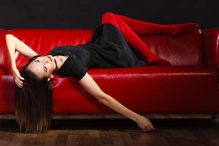 Elegant fashion outfit. Fashionable woman long legs in red vivid color pantyhose relaxing on couch indoor on black photo