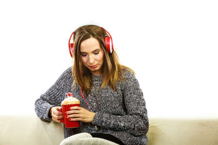 deep thought: People leisure relax concept. Woman casual style red big headphones listening music mp3, sitting on couch with mug in deep thought