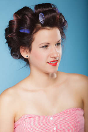 coif: Girl preparing to party. Headshot of  young woman with hair curlers pin up makeup studio shot on blue Stock Photo