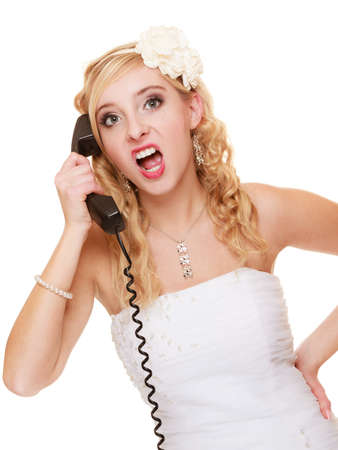 fury: Wedding relationship difficulties. Angry woman talking on the phone. Fury bride screaming isolated on white.