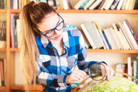 Education travel and geography concept. Young lovely woman female student in blue glasses in library pointing to globe photo
