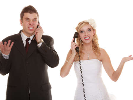 relationship difficulties: Wedding relationship difficulties. Angry woman and fury man talking on phone. Couple bride groom quarrelling screaming isolated on white. Stock Photo