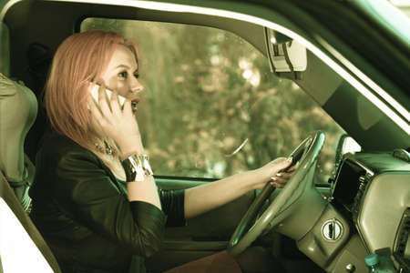 irresponsible: Concept of danger driving. Young woman driver redhaired girl talking on mobile phone smartphone while driving the car. Stock Photo