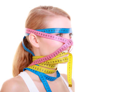 obsessive: Time for diet slimming weight loss. Health care healthy lifestyle. Fit fitness woman with a lot of colorful measure tapes around her head. Obsessed girl by body.