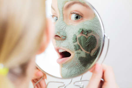 purifying: Skin care. Woman in clay mud mask on face with heart symbol of love on cheek looking in the mirror. Girl taking care of dry complexion.