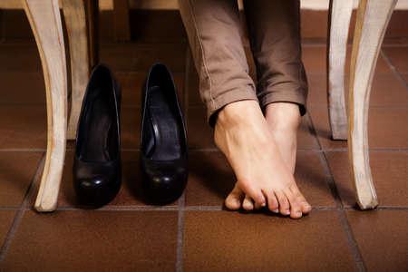 ragazze a piedi nudi: Bare piedi femminili sotto il tavolo annata retro bianco. Tired businesswoman donna ragazza con i crampi alle gambe di relax senza tacchi alti.