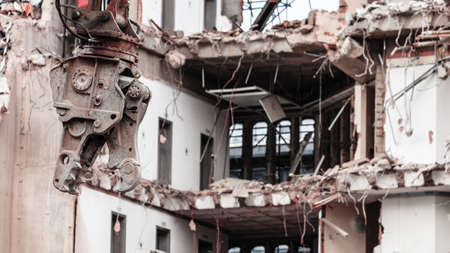 Urban scene. Dismantling of a house. Building demolition and crashing by machinery for new construction. Industry. photo