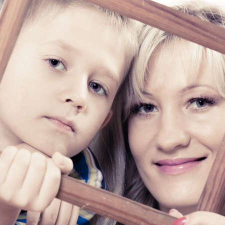 middleaged: Happy family and love concept. Portrait of middle-aged mother with son little boy holding frame decorations Stock Photo