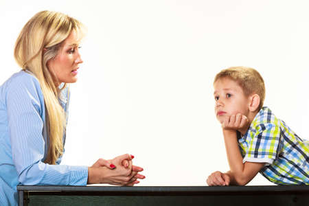Parenthood  domestic life and children upbringing. Mother talking with son little sad boy isolated on white background