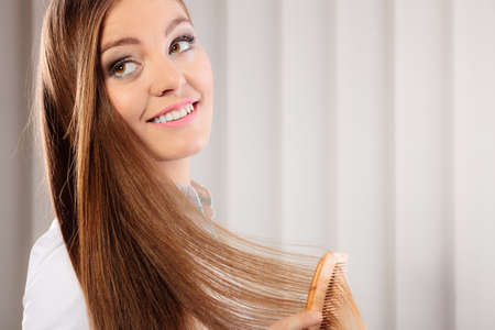 hair treatment: Health and beauty concept - young business woman refreshing her hairstyle she combs her long hair