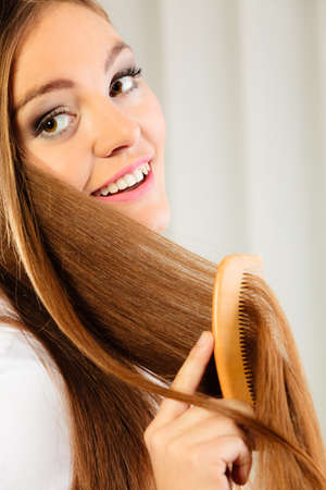 Health beauty and haircare concept - Closeup young business woman refreshing her hairstyle she combing her long brown hair with wooden comb photo