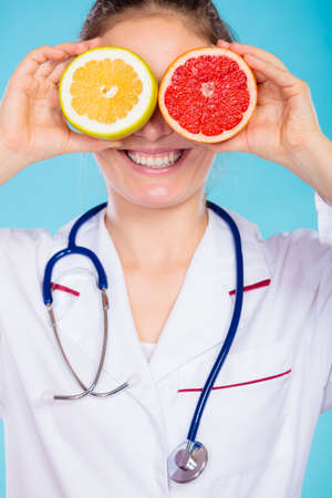 Health concept. Nutritionist doctor holding fruits slices for her eyes on blue. Dietitian recommending healthy food. Diet.