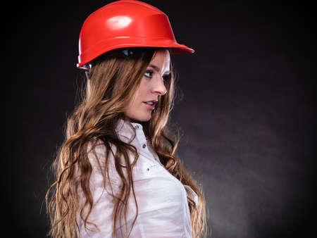 feministische: Vrouw in mannelijke specialiteiten. Meisje in rode helm. Veilig door het werk concept. Sexy jonge feministische op een zwarte grijze achtergrond.