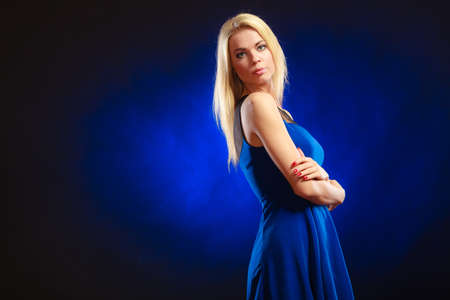 Party, new year, celebration, disco concept - Portrait attractive fashion woman, blonde long hair girl in evening dress night club dark blue background photo