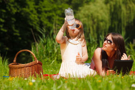 happy family concept: Summer children and happy family concept. Mother and daughter little girl having picnic in park outdoors.