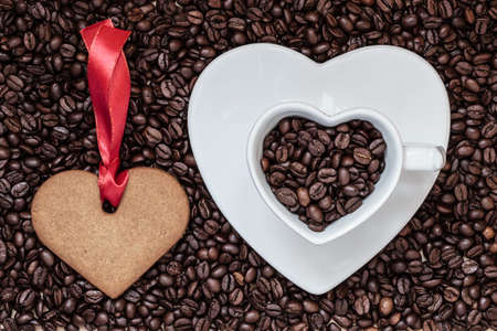 Coffee time concept. Heart shaped cup plate and cookie gingerbread on coffee beans background. Top view photo