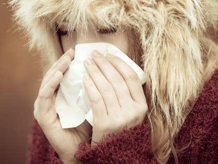 flue season: Flu cold, allergy symptom or other virus. Sick woman walking outdoor sneezing in tissue. Health care. Stock Photo