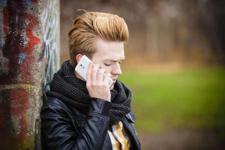 Technology and communication. Young fashion man talking on mobile cell phone using smartphone outdoor photo