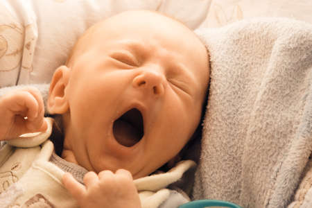 child crying: Closeup little newborn baby girl three weeks lying in diaper with open mouth
