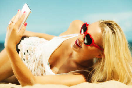 Technology and communication. woman texting on mobile phone, using smartphone reading sms or taking photo of herself on beach photo