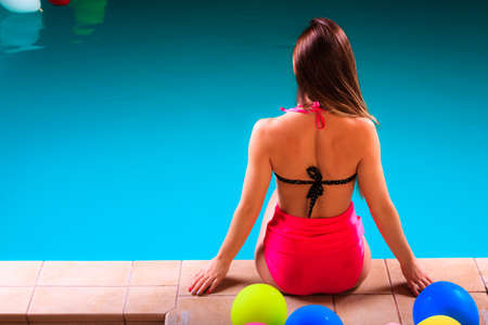 spa relax: Spa relax and holidays concept. Attractive woman in swimsuit back view. Fit female body, girl sitting at poolside