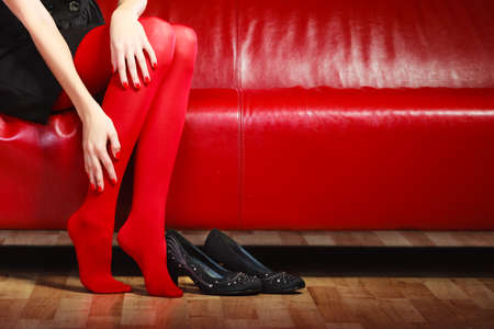 Elegant fashion outfit. Fashionable woman long legs in red vivid color pantyhose black shoes sitting on couch indoor photo