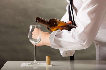 butler: Male waiter or butler serving pouring wine into glass.