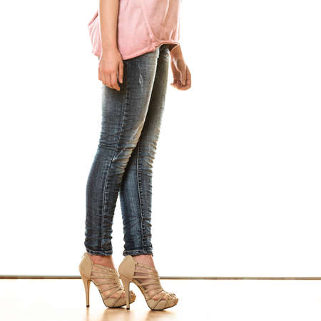 Fashion and people concept. Woman legs in denim trousers platform high heels shoes casual style isolated on white background photo