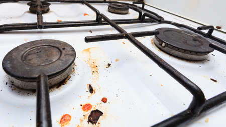 Housework, hygiene and cleaning concept. Dirt at home. Dirty filthy gas stove in kitchen photo