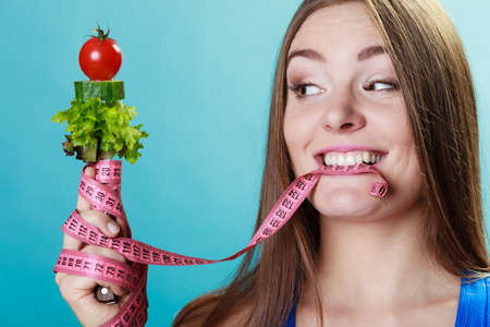 lose weight: Dieting weight loss concept. Sporty girl fitness woman holding fork with fresh mixed vegetables and measuring tape on blue background